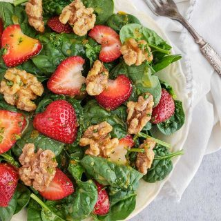 Spinach salad with sliced strawberries and walnuts in a white bowl with a napkin and fork.