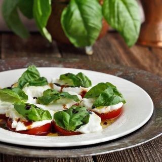 Tomatoes, basil and buffalo mozzarella on a white plate sitting on a wood table.