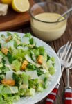 Close-up of Caesar Salad in a white bowl with salad tongs and dressing beside it.