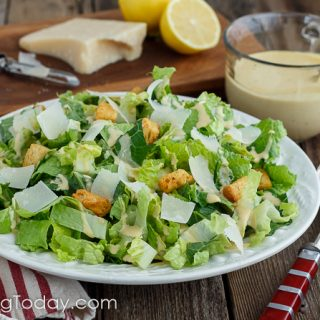 Romaine lettuce dressed with Caesar dressing in a white bowl over a red striped towel with parmesan and lemon on a cutting board in the background. A cup of the dressing in beside the bowl.