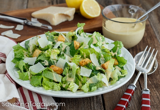 Romaine lettuce dressed with creamy Caesar dressing in a white bowl over a red striped towel with Parmesan and lemon on a cutting board in the background.