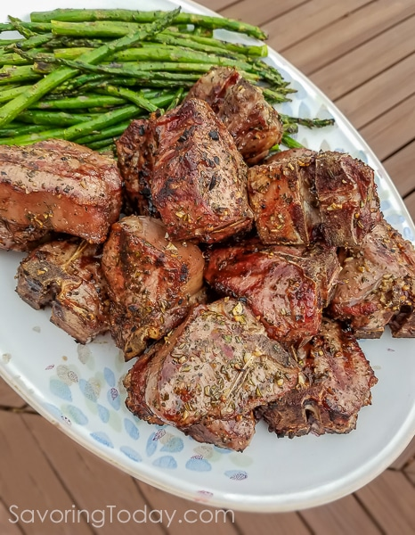 Grilled lamb chops piled on a platter with grilled asparagus.