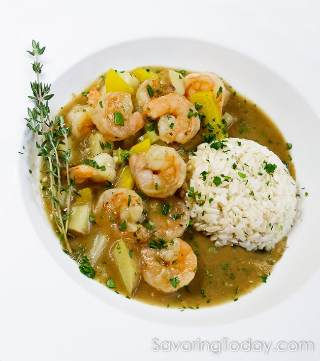 Shrimp stew with brown rice garnished with fresh thyme twigs in a white bowl.