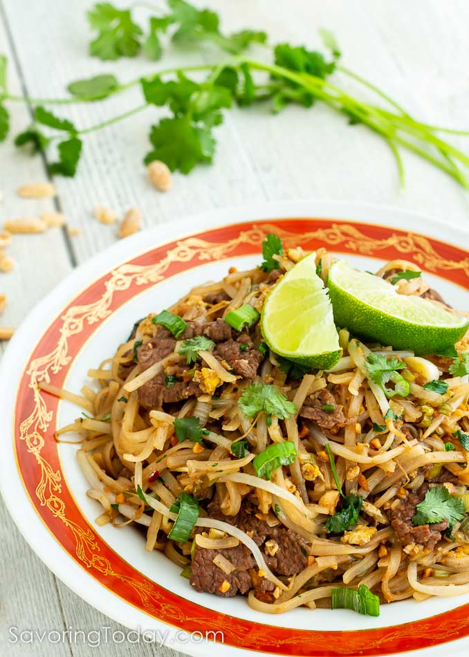 Beef Pad Thai in a bowl with lime wedges on top.