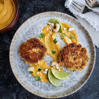 Crab cakes on a swirl of mango-lime cashew sauce with lime wedges.