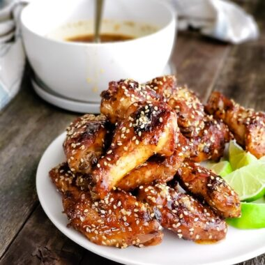 Chicken wings with Thai Chili Sesame Sauce served on a white plate with lime wedges.