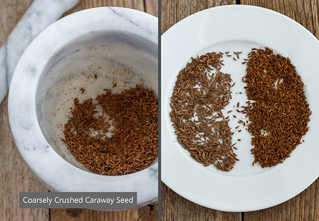 Crushed caraway seeds in a mortar and pestle beside the seeds on a white plate.