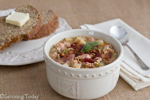 Salmon Dill Chowder in a white bowl with bread and butter on the side.
