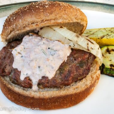 Green chile burger with salsa may and grilled onions on a whole wheat bun served on a white plate.