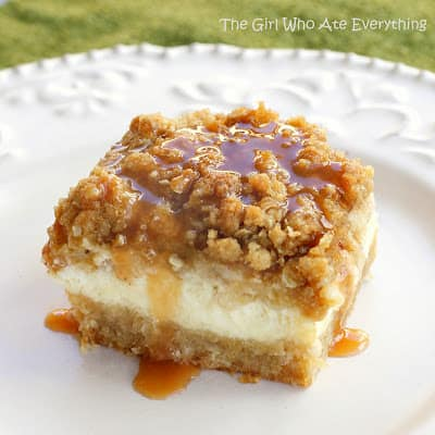 Cheesecake layered between a shortbread crust and crumb topping with caramel sauce dripping down the side. Caramel Apple Cheesecake Bars by The Girl Who Ate Everything