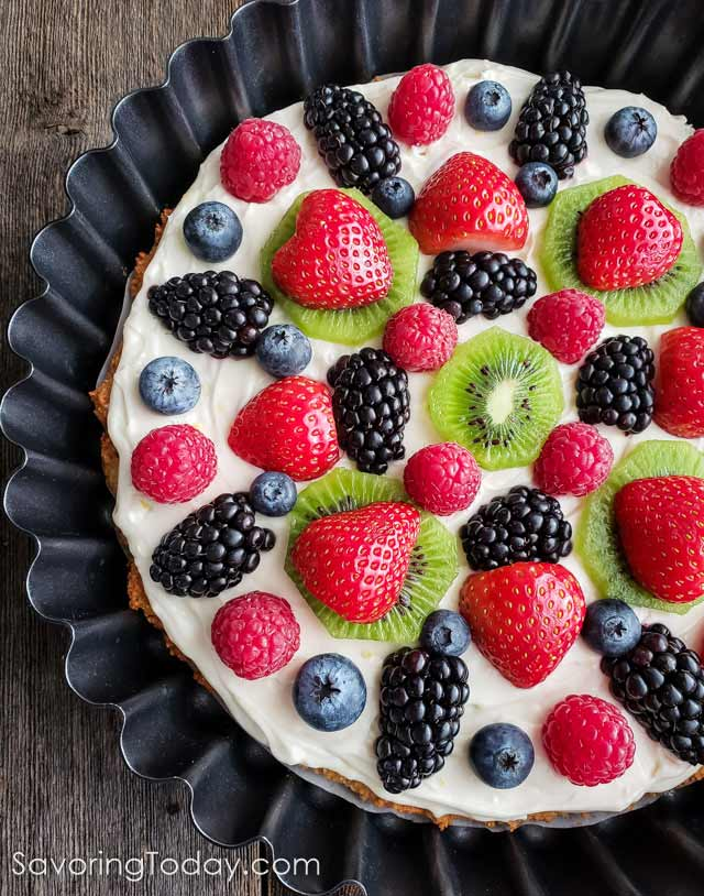 Gluten-Free Cream Cheese Fruit Tart without glaze in a tart pan on a wood table.