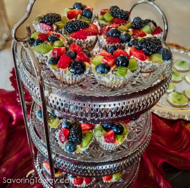Mini tarts with cream cheese, berries, and kiwi on tiered silver trays.