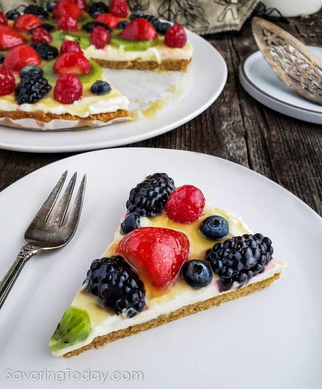 Fruit tart on a white plate on a wood table.