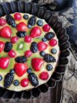 Fruit tart with blackberries, raspberries, blueberries, strawberries and kiwi on a cream cheese filling in a dark tart pan.