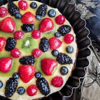 Fruit tart with blackberries, raspberries, blueberries, strawberries and kiwi on a cream cheese filling in a dark tart pan.