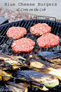 burgers on a charcoal grill with corn on the cob still in the husks