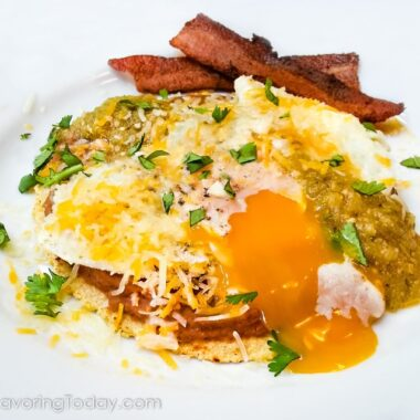 Huevos rancheros on a white plate with the egg yolk running over the side of the stack.
