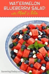 Watermelon and blueberry salad with mint and feta in a white bowl with blue trim.