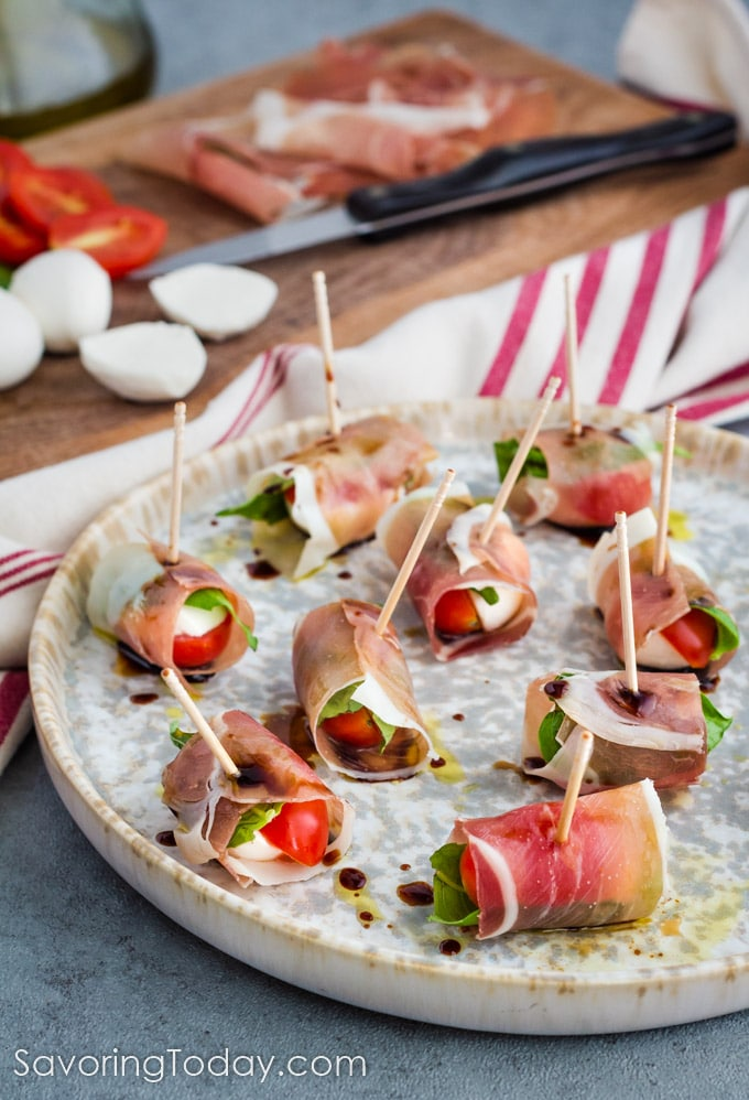 Tomato, mozzarella and basil wrapped with prosciutto on a tray for a party.