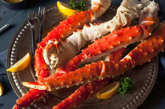 King crab legs on a metal platter with lemon slices and crab forks.