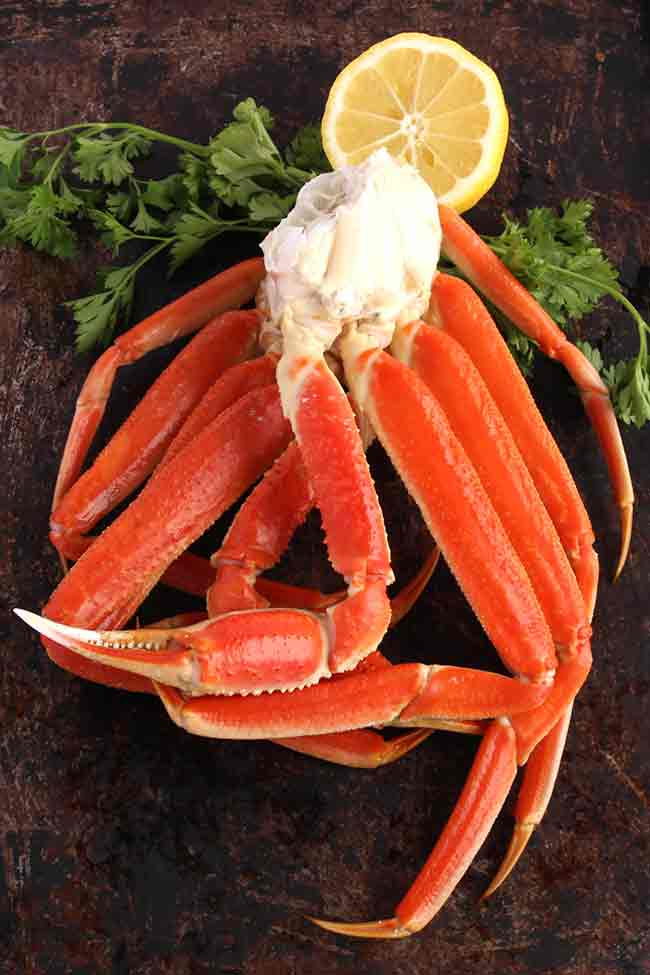 Snow crab legs on a brown tables with parsley and lemon.