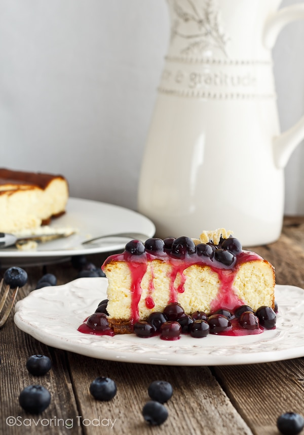 New York Cheesecake with blueberry topping on a white plate sitting on a table