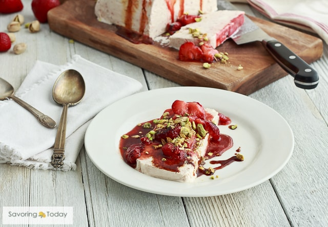 Creamy, frozen dessert with grilled strawberries and pistachios on a plate with the semifreddo behind it on a cutting board.
