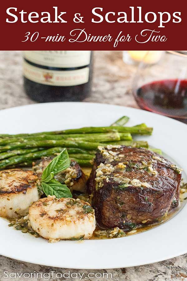 Pan-seared steak and scallops on a white plate with wine.
