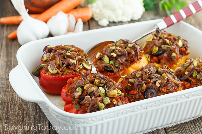 Red and orange bell peppers stuffed with sausage, cauliflower, and black olives, topped with caramelized onions and pistachios. Peppers are arranged in a white ceramic baking dish and serving spoon with garlic, carrots and cauliflower in the background.