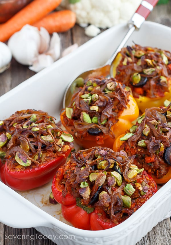 Stuffed red and yellow bell peppers topped with caramelized onions and pistachios in a white ceramic baking dish and serving spoon.