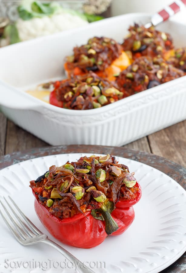 A stuffed red bell pepper topped with caramelized onions and pistachios on a white plate with a fork. Pan of stuffed peppers in the background.