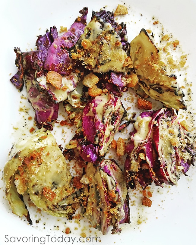 Grilled Cabbage with classic Caesar Dressing and Crushed Croutons sprinkled on top.