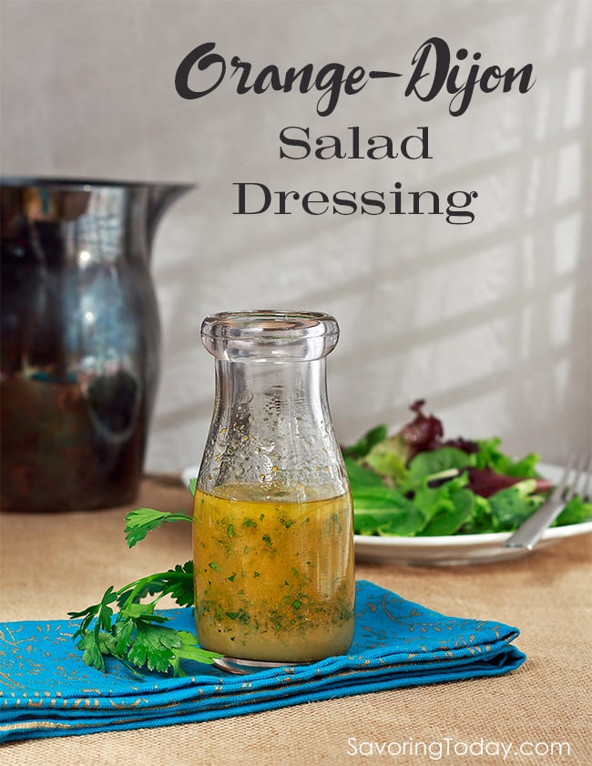 Orange-Dijon salad dressing with specs of parsley in a glass bottle on a blue cloth napkin.