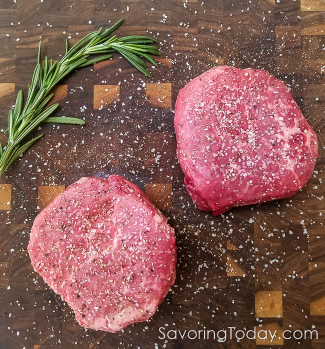 Raw tenderloin steak seasoned with sea salt and ground pepper.