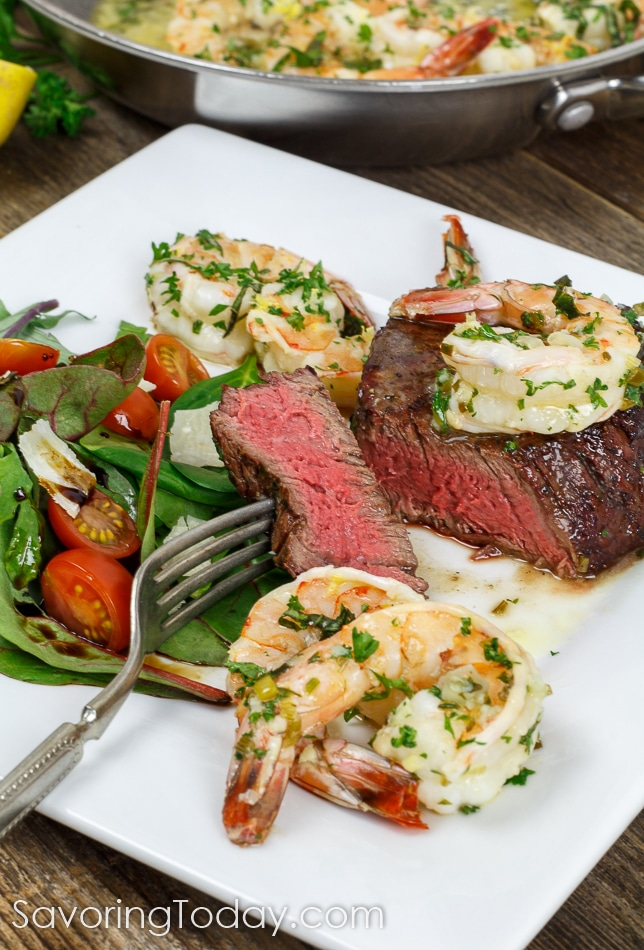 Grilled steak tenderloin topped with shrimp scampi and served with a garden salad. The rosy pink center shows the steak grilled to medium-rare. An amazingly simple date night meal for any skill level to impress their sweetheart!