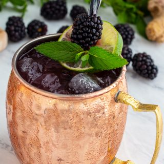 Ginger-Blackberry Cocktail in a copper mug garnished with blackberries, mint and lime.