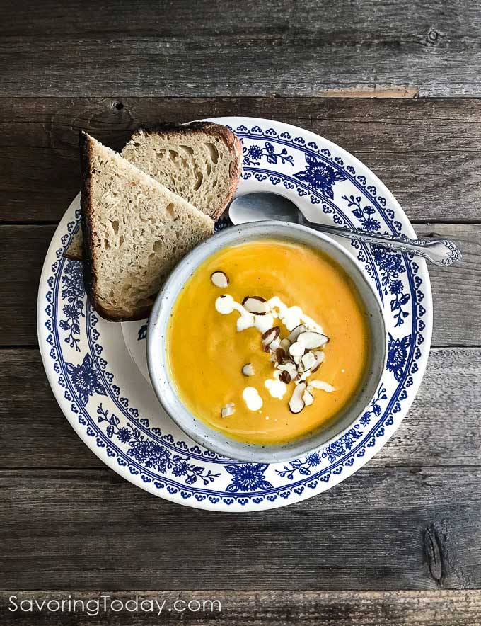 Butternut soup in a bowl on a blue and white plate with dipping bread.