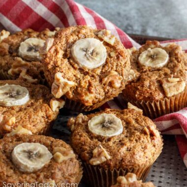 Sprouted wheat muffins with banana and walnut garnish stacked on a pan.