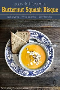 butternut squash soup in a bowl set in a blue and white plate with sliced bread