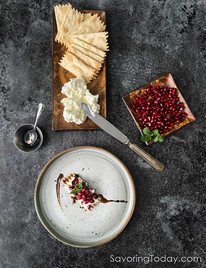 Ricotta and goat cheese spread on a rosemary cracker garnished with pomegranate and balsamic.