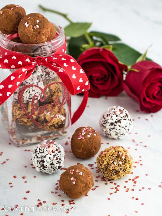 Homemade chocolate truffles in a jar with a red ribbon and white hearts for a Valentine gift.