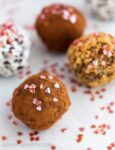 Close up of pink hearts sprinkled on chocolate truffles for Valentine's Day