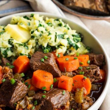 Irish beef stew and carrots with mashed sweet potatoes and kale in a beige bowl.