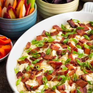 Artichoke dip in a white dish topped with green onions and bacon beside chips and veggies.